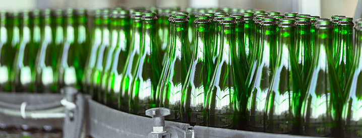 A line of green high-quality bottles on a manufacturing line