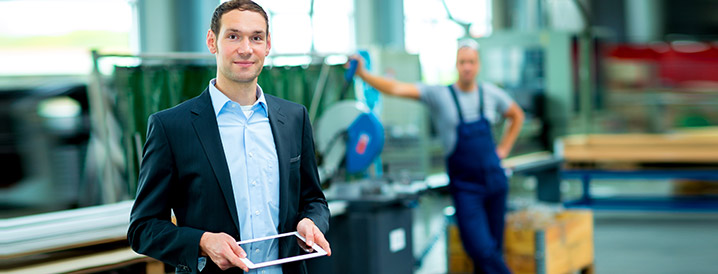 A smiling man in a manufacturing warehouse holding an ipad that contains real-time SPC process data